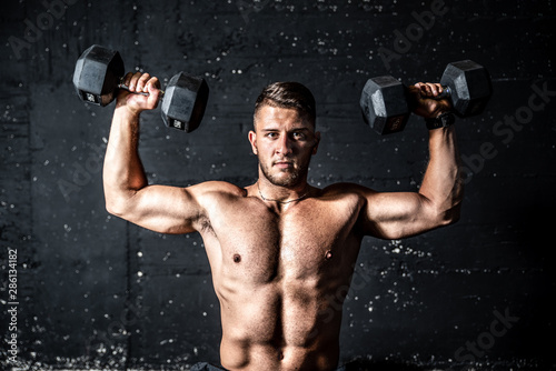 Fototapeta Young strong sweaty man shoulders workout training with two dumbbells in the gym dark image with shadows obraz