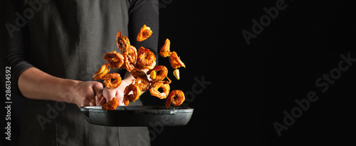 Professional chef prepares shrimps or langoustines with spices. Cooking mediterranean seafood, healthy vegetarian food on a dark background. With copy space for text - 286134592