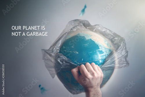 Fotomural  A man breaks a garbage bag which is wrapped globe of planet Earth