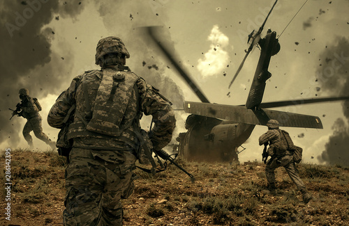 Photographie  Military helicopter and forces between fire and dust in the battlefield