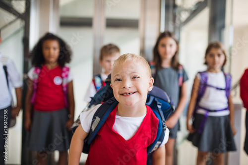 Fototapeta A down-syndrome school boy with group of children in corridor, walking. obraz