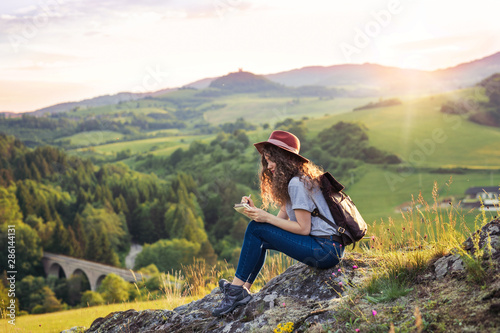 Foto auf Gartenposter Lineale Wachstum Young tourist woman traveller with backpack sitting in nature, writing notes.
