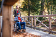 canvas print picture Senior father with wheelchair and his son on walk in nature.