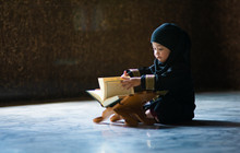 Asian Indonesian Muslim Kid Is Reading The Quran. The Quran Is Indicated As The Guided Book For All Muslim And It Is Direction  To Be On The Heaven Of God.Mosque,Islam,religion And Knowledge Concept
