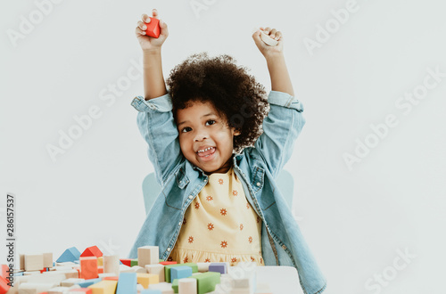 Fotografia, Obraz Cute little african american girl enjoy playing with colorful toy blocks on the table  at preschool