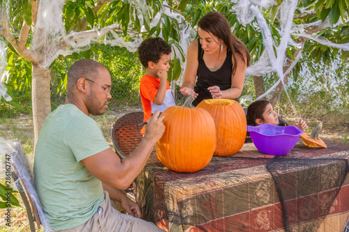 Fotografija Halloween pumpkin carving is a family tradition in the backyard