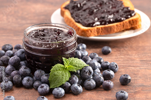 Photo AJar of Homemade Blueberry Jam on a Rustic Wooden Table
