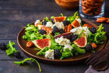 Salad with figs, feta cheese and blackberries in a wooden plate on dark background.