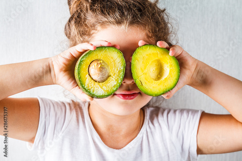 Healthy baby food concept. Girl child holds sliced avocado in place of the eyes.