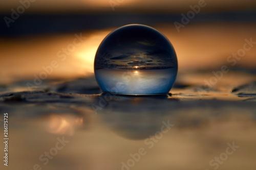 Foto auf AluDibond Zen glaskugel in der sich der sonnenuntergang im meer spiegelt