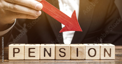 Fototapeta A man holds an arrow down over wooden blocks with the word Pension. Fall / reduction pension payments. Retirement. Financing retirees. Reduction of the pension fund. The low size of pensions. obraz