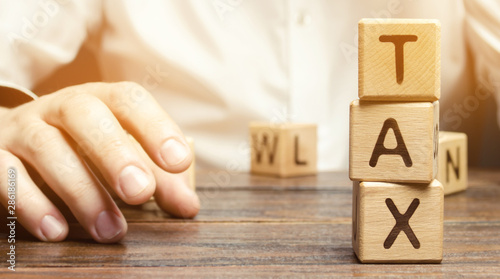 Fototapeta Wooden blocks with the word tax and a businessman sitting at the table. Making the right decision. Time to pay taxes. The concept of annual taxation. Taxes on vehicles, property, purchases. State fee obraz