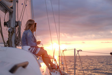 Couple Of Ladies Are Enjoying Their Trip On Sailing Boat While Drinking Wine And Watching Beautiful Sunset.