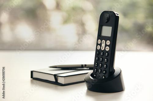 Obraz Telefono inalambrico y libreta con fondo verde fuera de foco y luz natural - fototapety do salonu