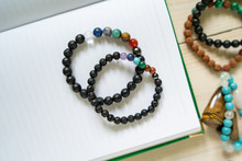 High Angle View On Crystal Semiprecious Stone Beads Bracelets Gems Natural Stones For Manifesting And Healing Energy Handmade For Good Fortune On The Table On Notebook