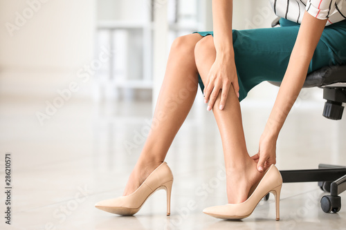 Young woman feeling ache because of wearing high heels in office Obraz na płótnie