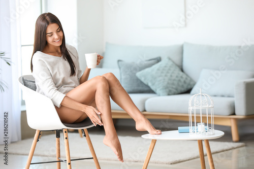 Fototapeta Young woman with beautiful legs at home