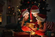 Cute Little Children Opening Magic Christmas Gift At Home