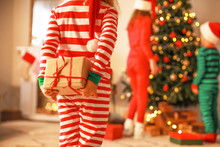 Little Girl Hiding Gift Behind Her Back On Christmas Eve