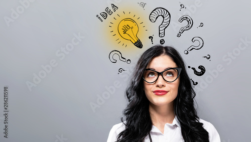 Fotomural Idea light bulbs with question marks with young businesswoman in a thoughtful fa