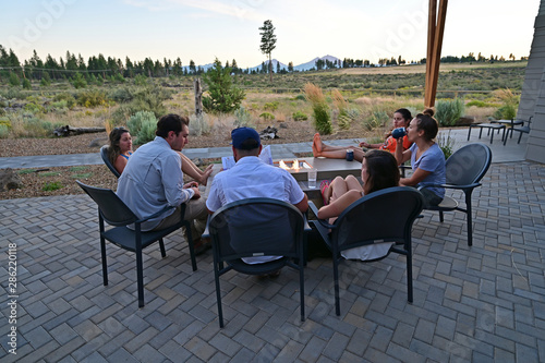 Obraz na plátne Six friends around a fire pit enjoy afternoon view of landscape around Sisters, Oregon on a perfect summer afternoon
