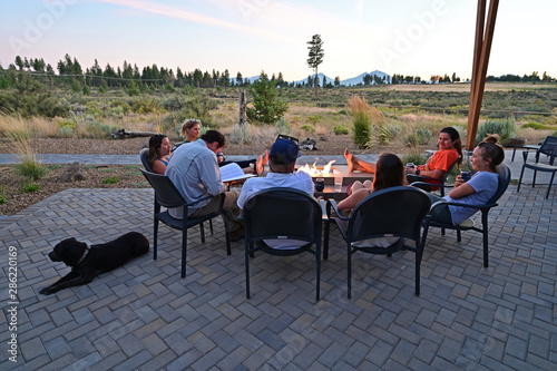 Fotografie, Obraz  Six friends around a fire pit enjoy afternoon view of landscape around Sisters, Oregon on a perfect summer afternoon