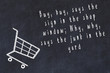 Chalk drawing of shopping cart and short quote about shopping on black board