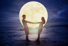 Young Couple Standing On Beach And Watching The Moon.Celebrate Mid Autumn Festival Concept
