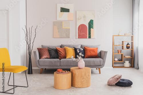 Yellow, orange, black and brown pillows on comfortable grey ...