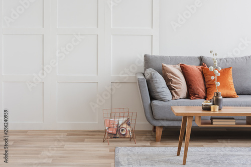 Poster Personal Copy space on empty white wall of fashionable living room interior with grey and orange design