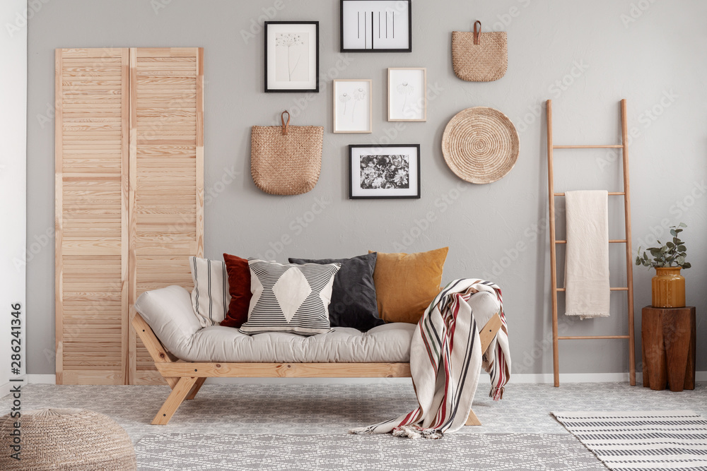 Fototapety, obrazy: Wooden and wicker accessories in fashionable scandinavian living room interior with futon sofa with pillows