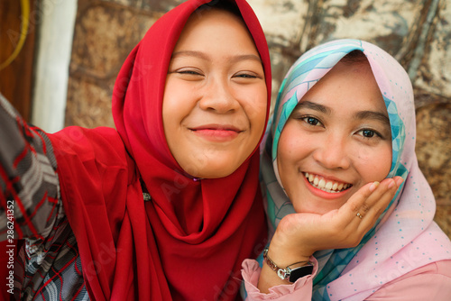 Fotografía  Happy and pretty Asian Indonesian girls in traditional Islamic hijab head scarf
