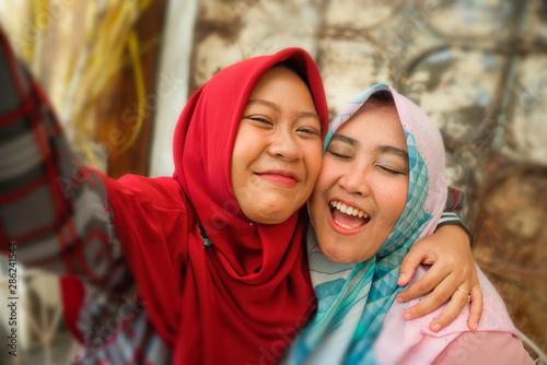 Fotografie, Obraz  Happy and pretty Asian Indonesian girls in traditional Islamic hijab head scarf