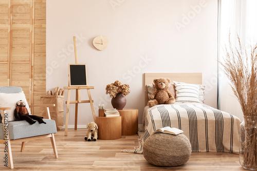 Teddy bear on single wooden bed in natural kid's bedroom Fototapet