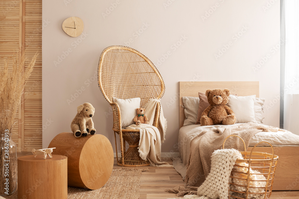 Fototapety, obrazy: Wicker peacock chair with pillow, armchair and toy in beige and wooden baby bedroom interior