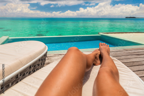 Obraz na plátně Suntan luxury vacation travel first person view woman sunbathing relaxing on sun lounger at hotel room