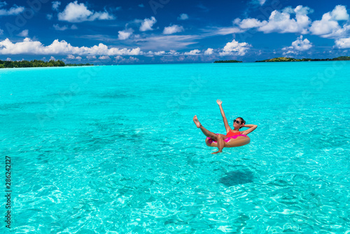 Leinwand Poster Beach winter holidays getaway vacation woman relaxing on pool float having fun swimming in ocean turquoise water