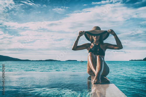 Foto op Plexiglas Spa Elegant black swimsuit model woman high end fashion with sun hat on infinity poolside luxury resort vacation for wellness spa concept, hair removal laser legs and body.