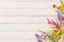 Wildflowers On White Wooden Background