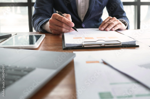 Accountant working with data documents calculating on business report, Selective focus Wallpaper Mural
