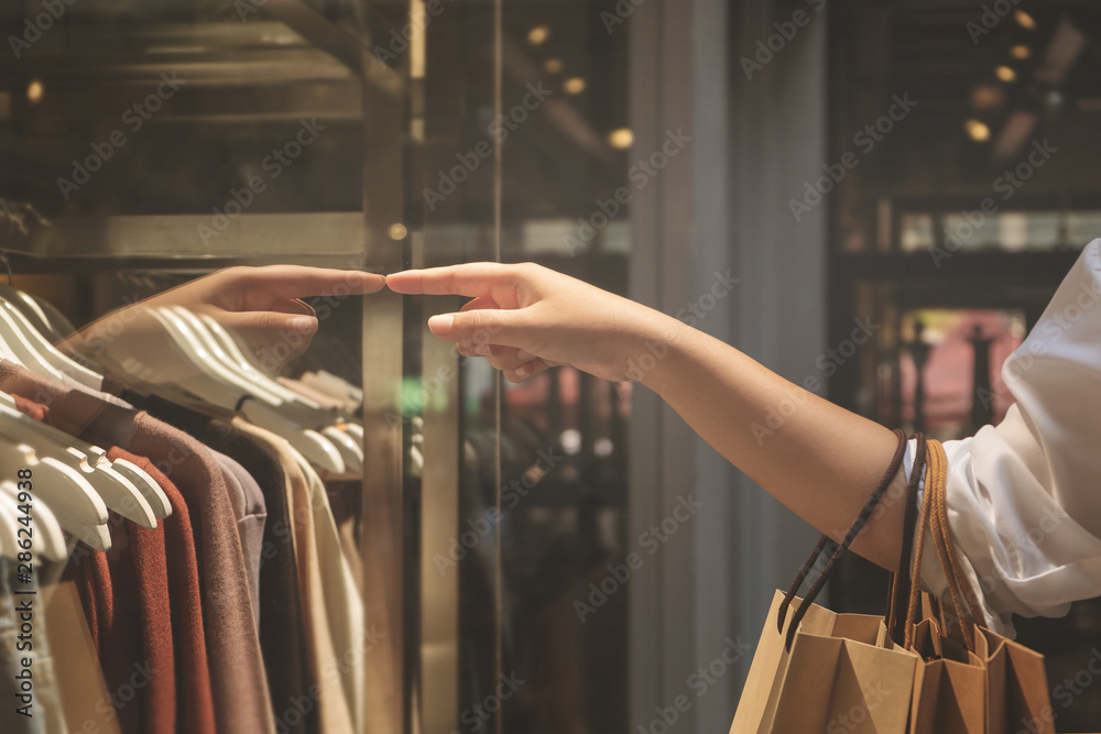 Fototapeta Hand of woman holding paper bags enjoy with shopping in the mall.