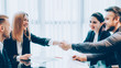 Professional cooperation. Business partners closing deal, shaking hands in modern conference room.