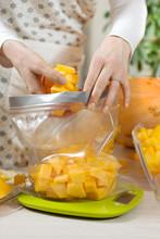 Kobieta Wkłada Pokrojoną W Kostkę świeżą Pomarańczową Dynię Do Worka Foliowego Przeznaczonego Do Przechowywania żywności. Torba Foliowa Stoi Na Wadze Kuchennej.
