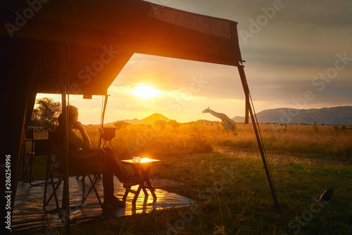 Obraz Woman rests after safari in luxury tent during sunset camping in African savannah of Serengeti National Park,Tanzania. - fototapety do salonu