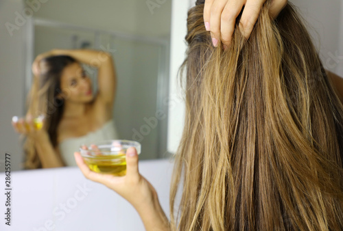 Fototapeta Young woman applying olive oil mask on hair in front of a mirror. Hair care concept. Focus on hair. obraz