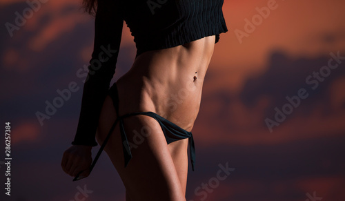 Sexy unrecognizable woman undress her panties on a cloudy sky background - 286257384