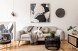 Leinwanddruck Bild - Stylish and scandinavian living room interior of modern apartment with gray sofa, design wooden commode, black table, lamp, abstrac paintings on the wall. Beautiful dog lying on the couch. Home decor.