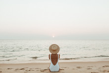 Summer Vacation Fashion Concept. Young, Tanned Woman Wearing A Beautiful White Swimsuit With A Straw Hat Is Sitting And Relaxing On Tropical Beach With White Sand And Is Watching Sunset And Sea.