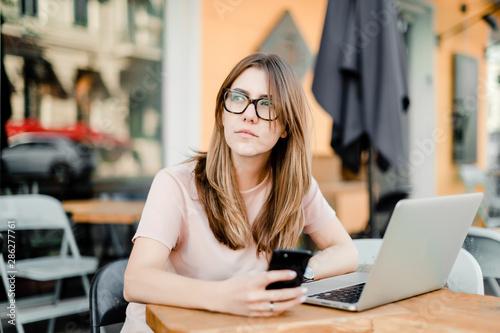 Fototapeta woman working remotely with laptop and phone in cafe obraz na płótnie