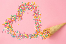 Empty Ice-cream Waffle Cone And Colorful Sprinkles On Pink Background, Heart Of Sweet Candy, Top View. Scattering Of Multicolored Sweets And Confectionery Topping.